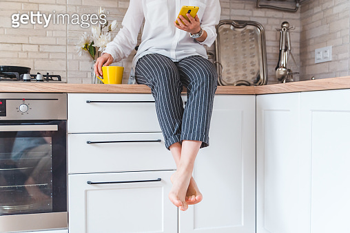 woman sitting on kitchen table with phone and yellow mug