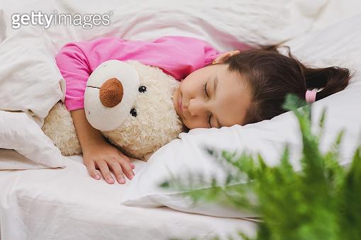 Cute little child girl sleeping with teddy bear