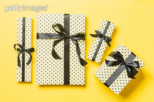 wrapped Christmas or other holiday handmade present in paper with Black ribbon on yellow background. Present box, decoration of gift on colored table, top view