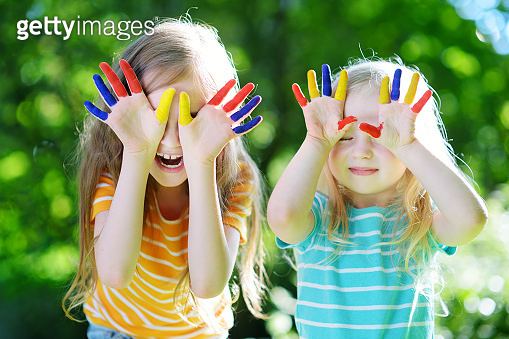 Adorable little sisters with their hands painted having fun outdoors