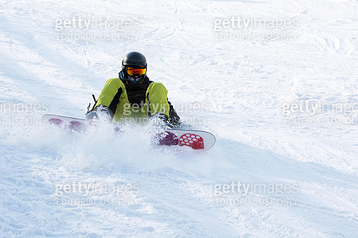 RUSSIA - MOSCOW 24.02.2018. Snowboarder learns to turn, ride and get up from snowboard.