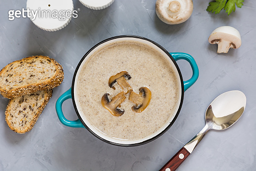 Mushroom champignon cream soup with toast on grey concrete table. View from above.