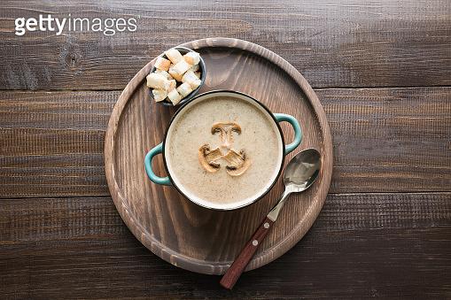Mushroom champignon cream soup on dark wooden board. View from above.