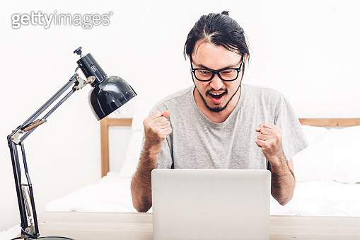 Happy man relaxing and using digital laptop computer on the bed at home.man checking social apps and working.wireless technology concept
