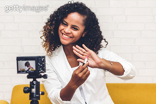 African american woman blogger in front of camera recording vlog herself talking about with makeup cosmetics for internet social networks at home