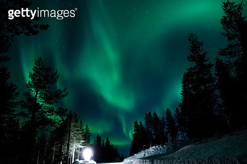 Large lamp illuminating the countryside for tourists to observe aurora borealis.