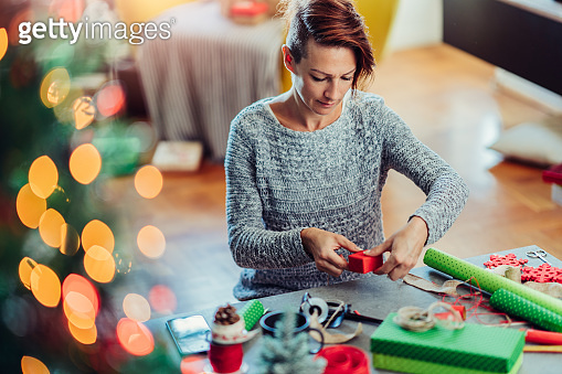 Woman wrapping Christmas presents in living room