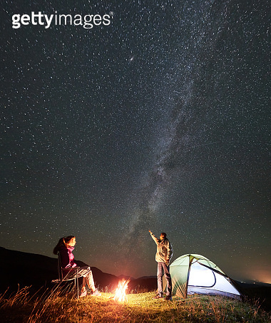 Couple tourists at night camp in mountains under starry sky