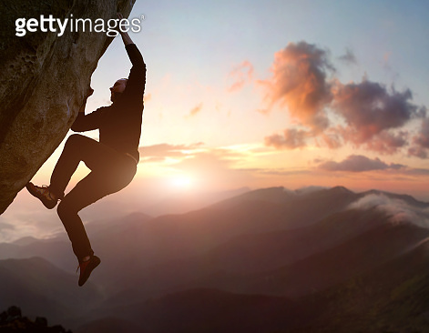 Rock climbing. Male climber trying staying on challenging rock, overcoming obstacles. Mountain and sunrise on background