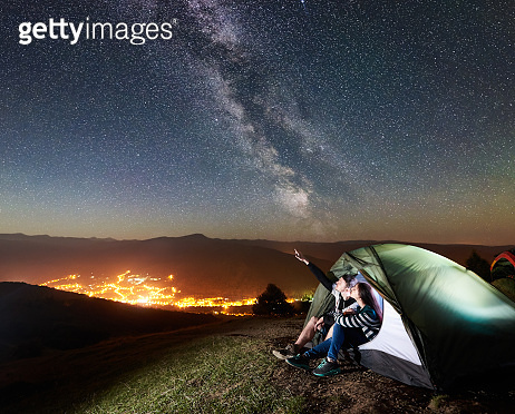 Couple tourists resting at night camping under stars