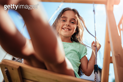 Low angle view of a little girl sitting on the swing at backyard
