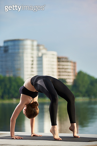 Slender girl in black sportswear practicing yoga outdoors near the river, standing in Upward bow Wheel pose