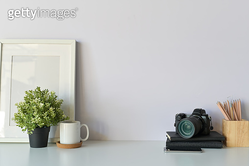 Photographer desk concept. designers table, photo camera, notebook paper, coffee and photo frame Copy space, background. - Image.