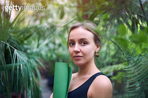 Portrait of cute young woman holding a rolled yoga mat in jungle. Sunny day