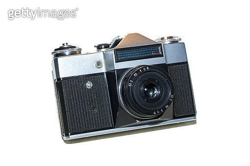 retro slr film photo camera, front angled view on white background. analog vintage film camera