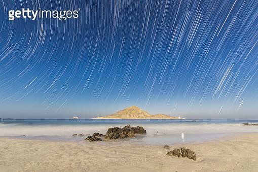 Milky way star trails nightscape at Atacama Desert coastal area. White sands at