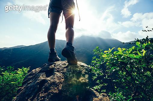 Successful hiker hiking at sunrise summer mountain top cliff edge