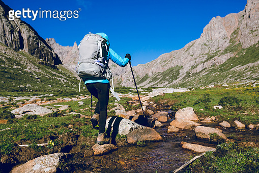 Woman hiker hiking on high altitude mountains