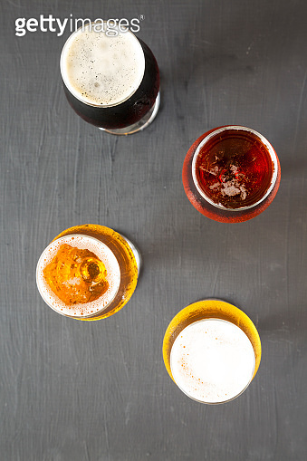 Cold craft beer assortment on a black surface, top view. Overhead, from above.