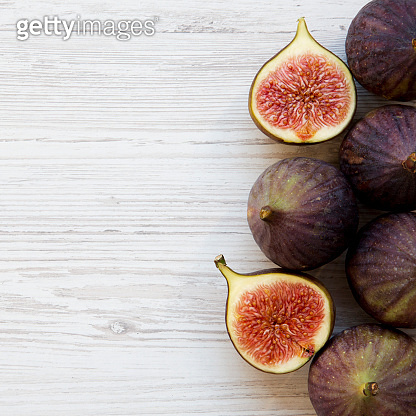 Fresh figs on white wooden background, top view. From above, overhead. Copy space.