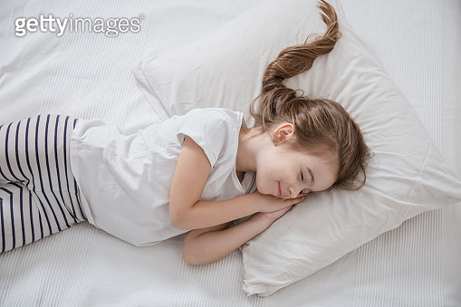 Cute little girl with long hair sleeping in bed.