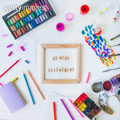 Top view creative art class concept. Canvas in frame with lettering inside and many colorful paintiing materials on white wooden background. Drawing lesson for children and adults. Flat lay. Square