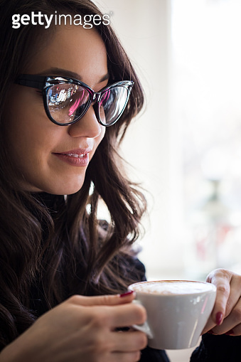 Woman hand holding cup of coffee in the cafe.