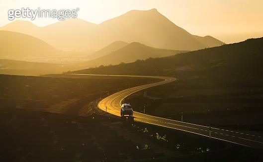 Sunlit road between mountains