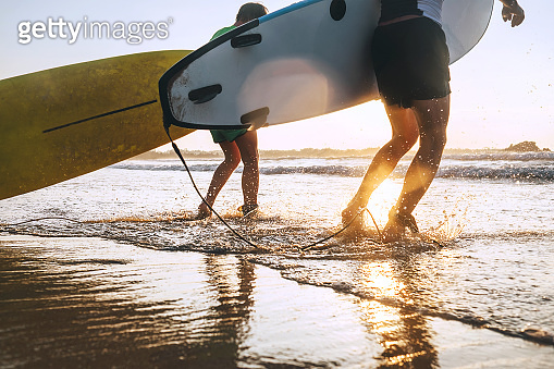 Son and father surfers run in ocean waves with surfing boards