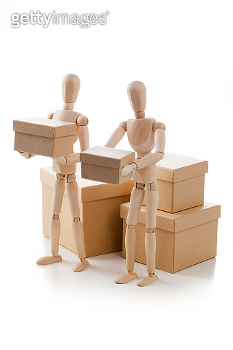 Two wooden mannequins carrying boxes isolated on white background