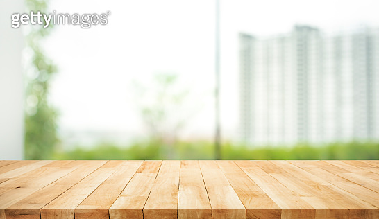Real wood table top texture on blur leaf tree garden and wall building from city,park