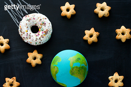 top view  handmade model  of Earth planet, donut meteorite   and cookies in the shape of stars on the chalkboard
