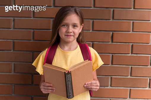 portrait of a little beautiful girl with a backpack holding a book