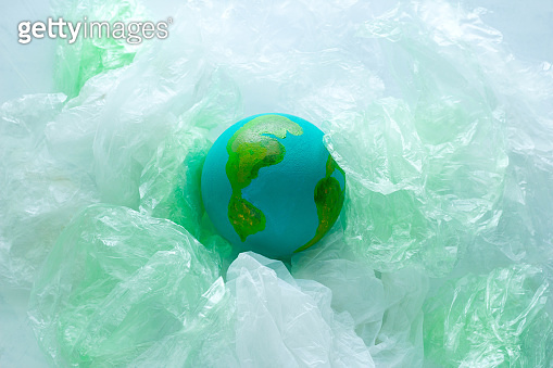 small model of the  Earth planet among plastic bags, environment, global pollution  concept, earth day