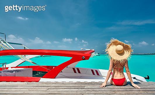 Woman in bikini sitting on jetty with boat