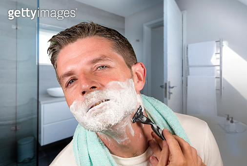 domestic lifestyle morning portrait of attractive and happy man shaving at modern apartment  bathroom his face covered with foam looking on the mirror in daily routine and masculinity concept