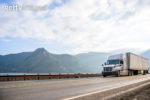 Powerful big rig semi truck with dry van semi trailer running with cargo in the road in Columbia Gorge
