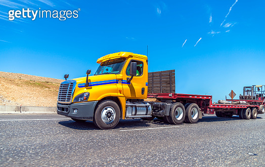 Yellow big rig day cab semi truck with step down semi trailer and forklift mounted at the end of the trailer running on the road to warehouse for loading