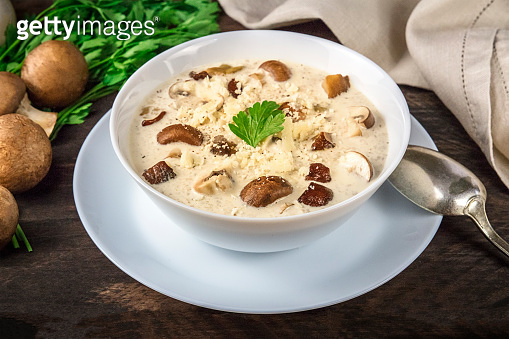 Mushroom soup with ingredients on a dark rustic wooden background, selective focus