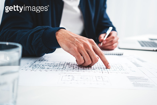 Coworker man using laptop and printer blueprint in modern office. Graph designer man working on workplace