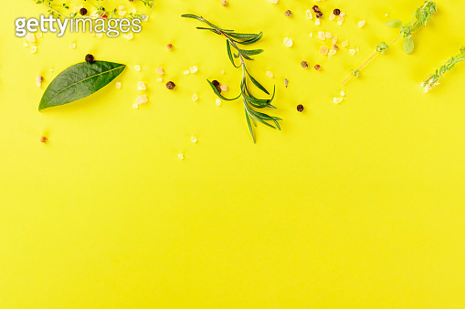 Herbs and spices, shot from the top on a yellow background with a place for text, recipe design template
