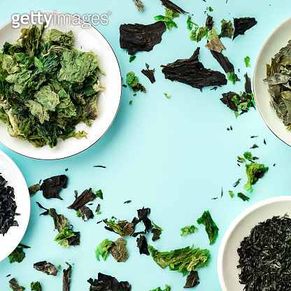 Various dry seaweed, sea vegetables, square overhead shot on a teal background forming a frame with a place for text