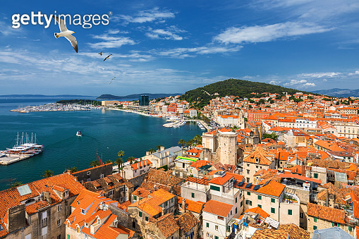 Split waterfront and Marjan hill aerial view, Dalmatia, Croatia. Panoramic summer cityscape of old medieval city Split, Croatia, Europe.  Traveling concept background. Seagull's flying over Split.