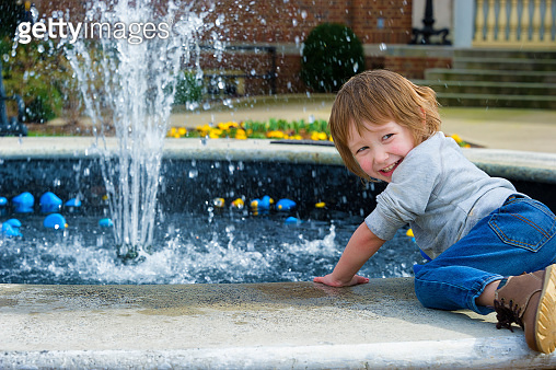 Boy playing with rubber ducks in fountain