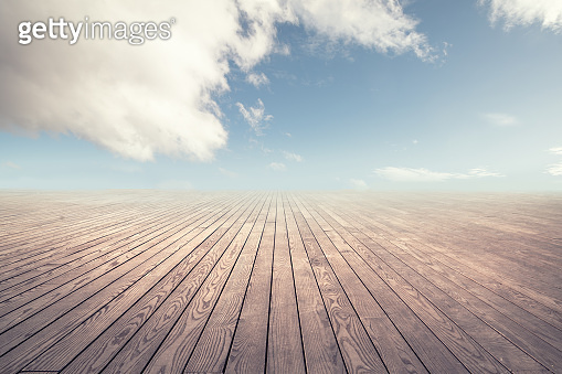 Empty wooden floor against cloudy sky with clouds.