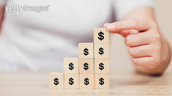Woman hand arranging wood block with icon money dollar,growth,finance and investment concept.