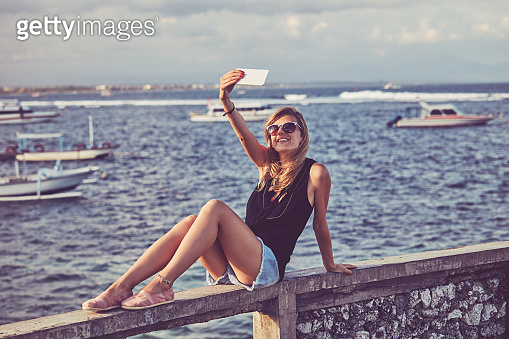 Attractive woman using cellphone while sitting near sea/ocean.