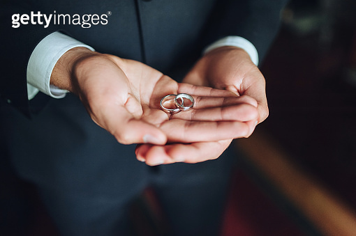 Two wedding rings on groom's palms. A man makes a marriage proposal.