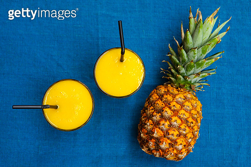 Pineapple juice, smoothie on blue background. Copy space. Top view.