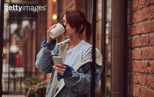 A beautiful tattooed girl wearing a denim coat drinks takeaway coffee holding a smartphone outside the cafe.
